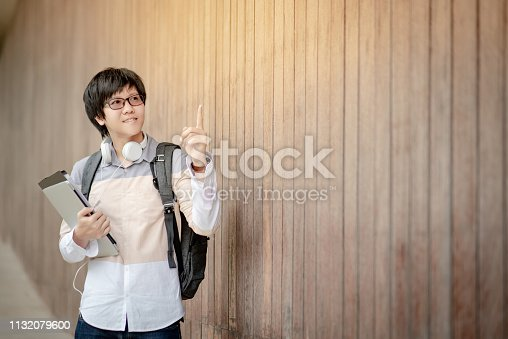 947303582 istock photo Asian man university student with glasses, headphones and backpack pointing finger up and holding laptop computer and file in campus building corridor. Education opportunity or scholarship concepts 1132079600