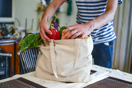 Asian man unpacking groceries at kitchen island. He is removing fruits and vegetables from reusable bags.