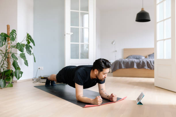 Asian man uses digital tablet to lean plank position Photo series of a japanese man working out at home, watching youtube videos and learning the exercises. exercising stock pictures, royalty-free photos & images
