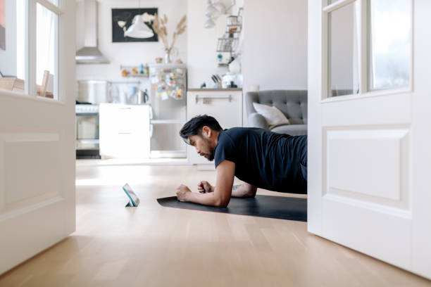 Asian man uses fitness app to learns fitness exercises stock photo