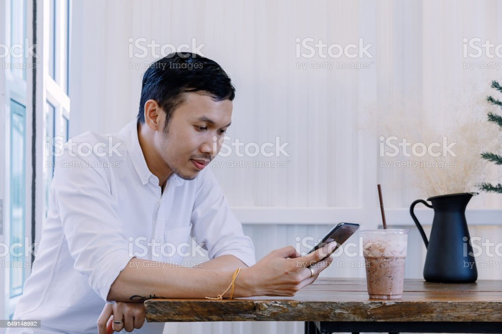 Asian man using a mobile phone and drink coffee in bakery shop. - Stock  image .