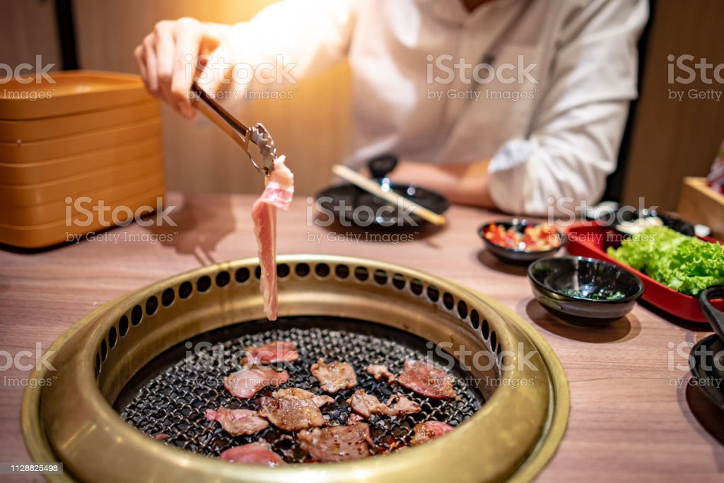 Asian Man Using Kitchen Tongs Grilling Beef And Bacon On Grill Plate Eating Korean Barbecue Buffet In The Restaurant Stock Photo Download Image Now Istock