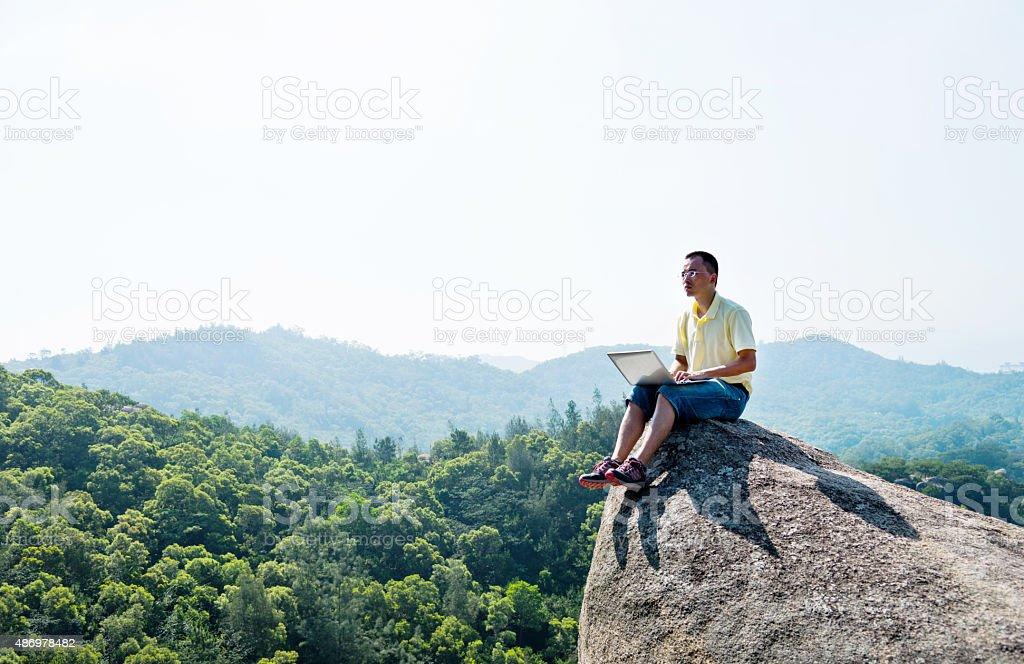 Asian man using laptop on rock stock photo