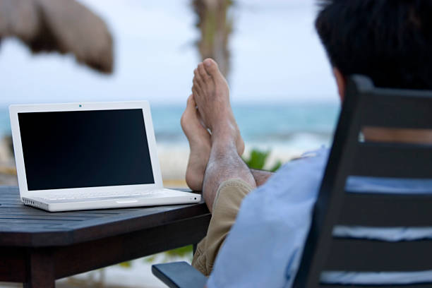 Asian Man Using Laptop Outside at Beach, Copy Space stock photo