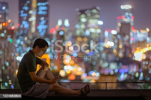 istock Asian man Using Mobile Phone In Downtown District 1024683804