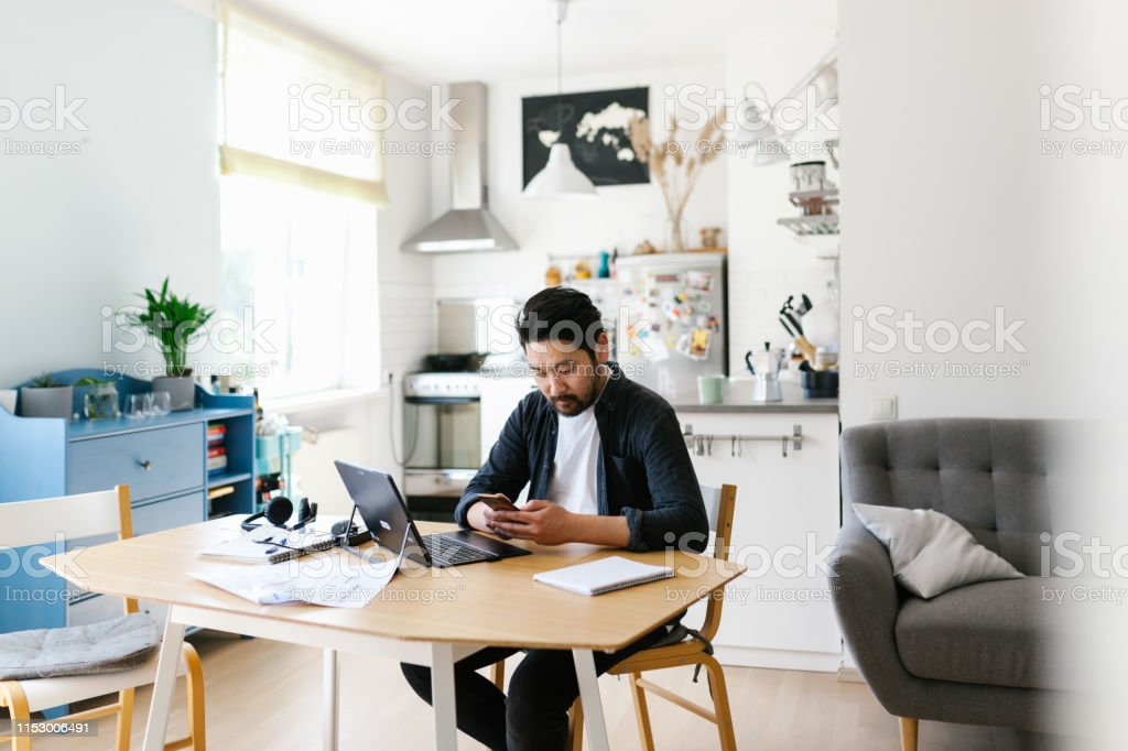 Asian man using smart phone while working from home - Royalty-free 35-39 Years Stock Photo