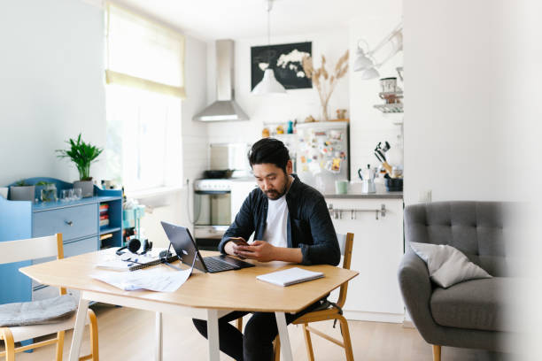 Asian man using smart phone while working from home stock photo