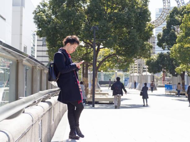 asian man waiting for his friends - prefektura kanagawa zdjęcia i obrazy z banku zdjęć