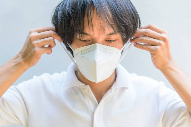 A asian man wear N95 mask for protect PM2.5 Dust and disease stock photo