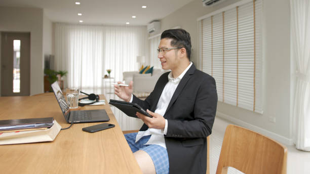 Asian man wearing a suit or business wear on top and sweatpants or boxers on bottom. Businessman video conference using laptop and tablet online meeting.Working from home and Working remotely. stock photo