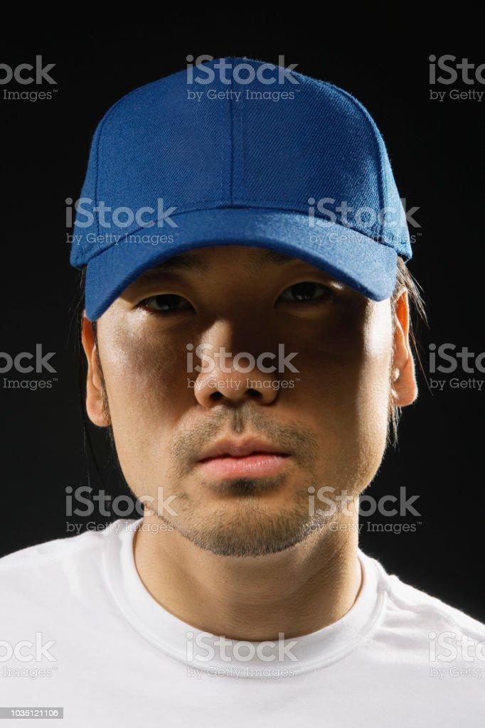 Asian man wearing baseball hat