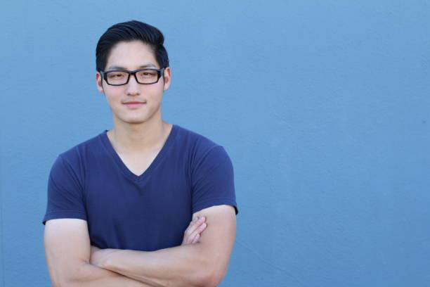 Asian man wearing glasses on blue background stock photo