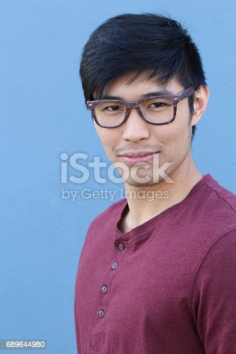 689644378istockphoto Asian man wearing glasses on blue background 689644980