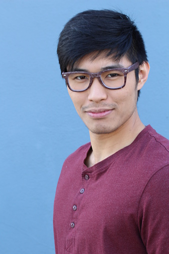 689644378 istock photo Asian man wearing glasses on blue background 689644980