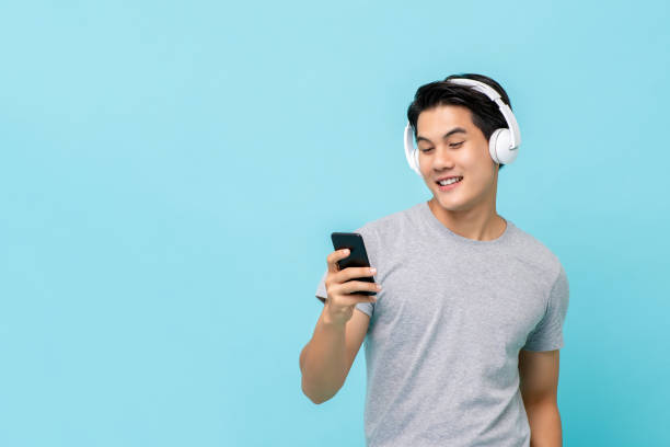 Asian man wearing headphones listening to music from smartphone stock photo