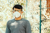istock Asian man wearing the N95 medical face mask due to coronavirus or covid-19 outbreak, outdoor - Person protecting from air contamination, coronavirus, sars cov 2 or viral infection by wearing mask. 1212664925