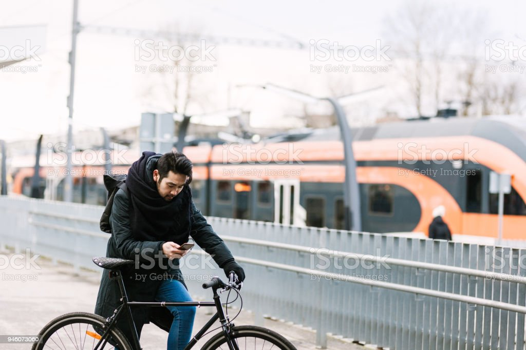 Asian man with bicycle in railroad station using smartphone stock photo