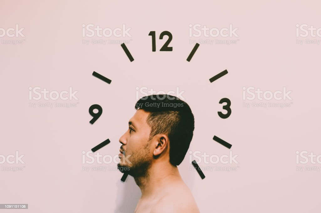 Asian man with black clock on white wall stock photo
