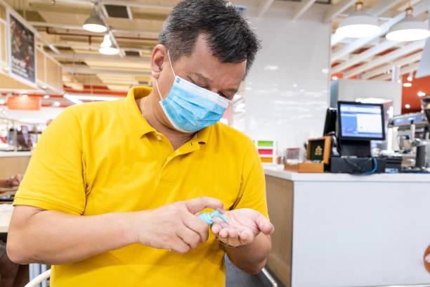 Asiatischer Mann mit Gesichtsmaske tragen Desinfektionsmittel Desinfektionsmittel auf die Hand vor dem Essen – Foto