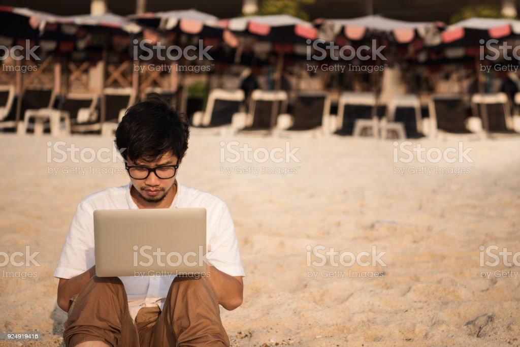 Asian man with his computer on the beach with waves from sea and...
