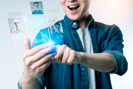 istock Asian man with hi-tech smart phone gadget technology work from home WFH, futuristic virtual hologram IOT internet of thing technology social network online meeting 1221404723