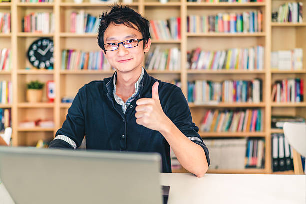 asian man with laptop, thumbs up, at home office, library - brille daumen hoch stock-fotos und bilder