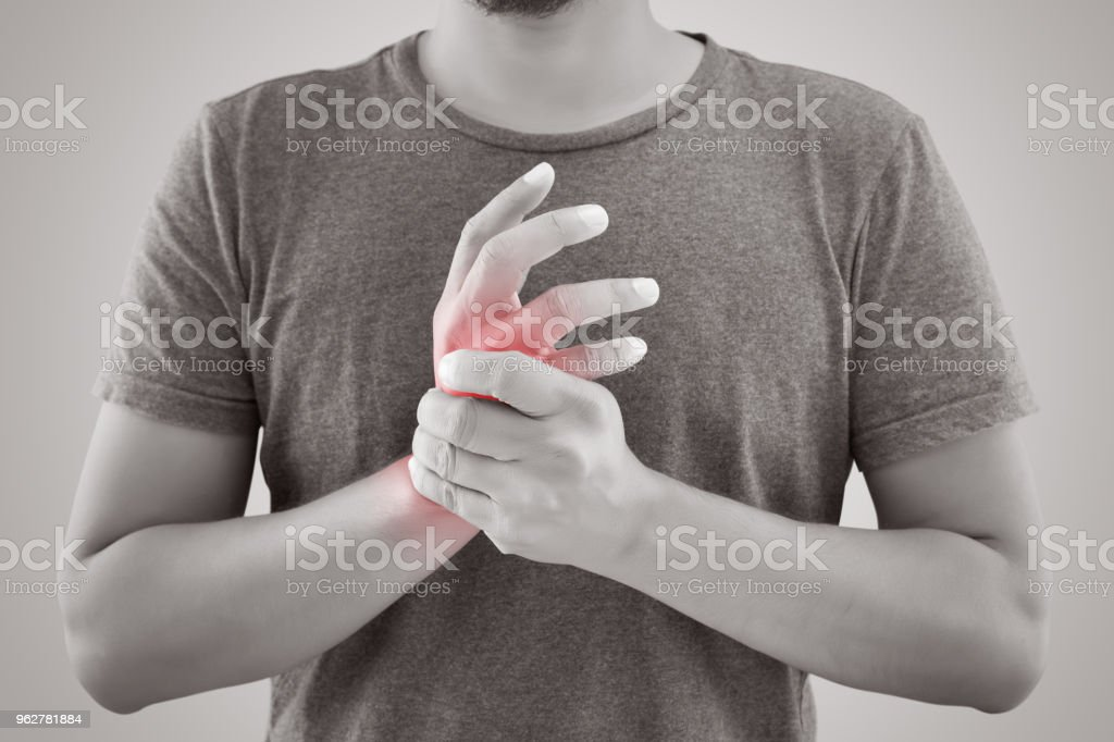 Asian man with pain in wrist against gray background stock photo
