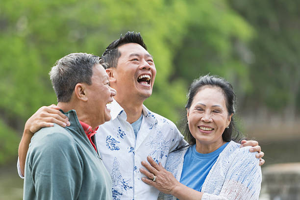 Asian man with senior parents in park laughing An Asian man standing in the park with his parents. The son is in the middle, with his arms around his parents shoulders. They are talking and laughing old mother son asian stock pictures, royalty-free photos & images
