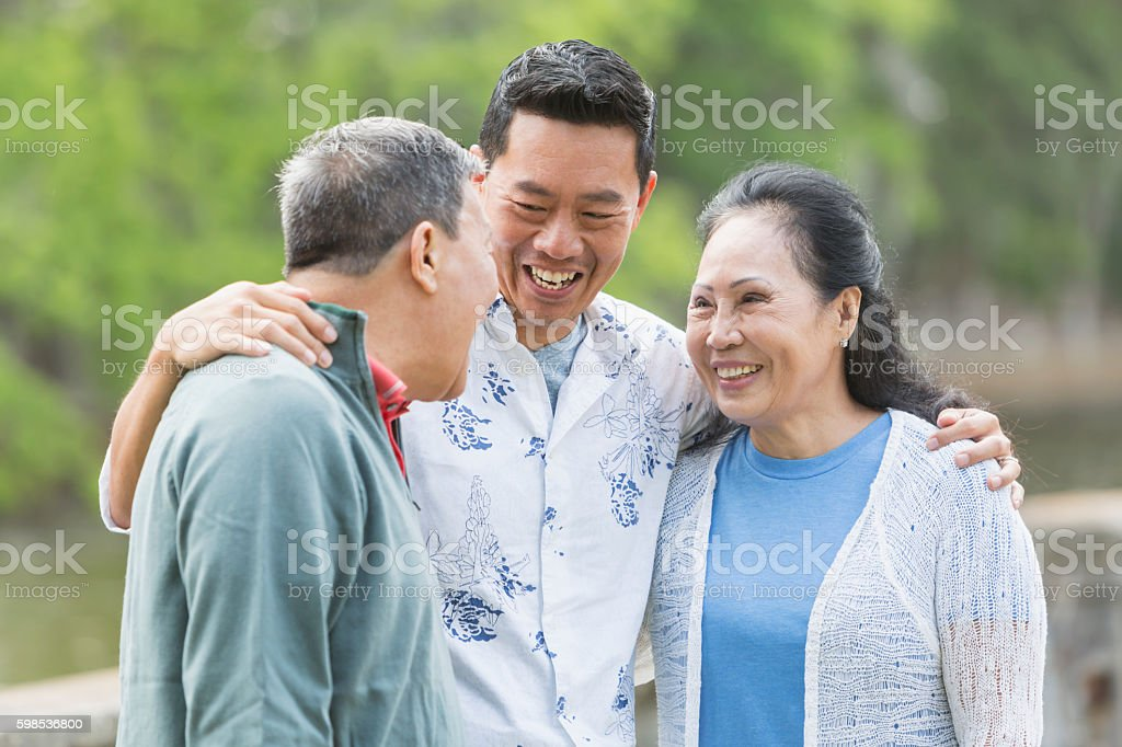 Asian man with senior parents in park talking stock photo