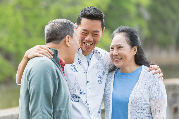 Asian man with senior parents in park talking An Asian man standing in the park with his parents. The son is in the middle, with his arms around his parents shoulders. They are looking at each other, talking. old mother son asian stock pictures, royalty-free photos & images