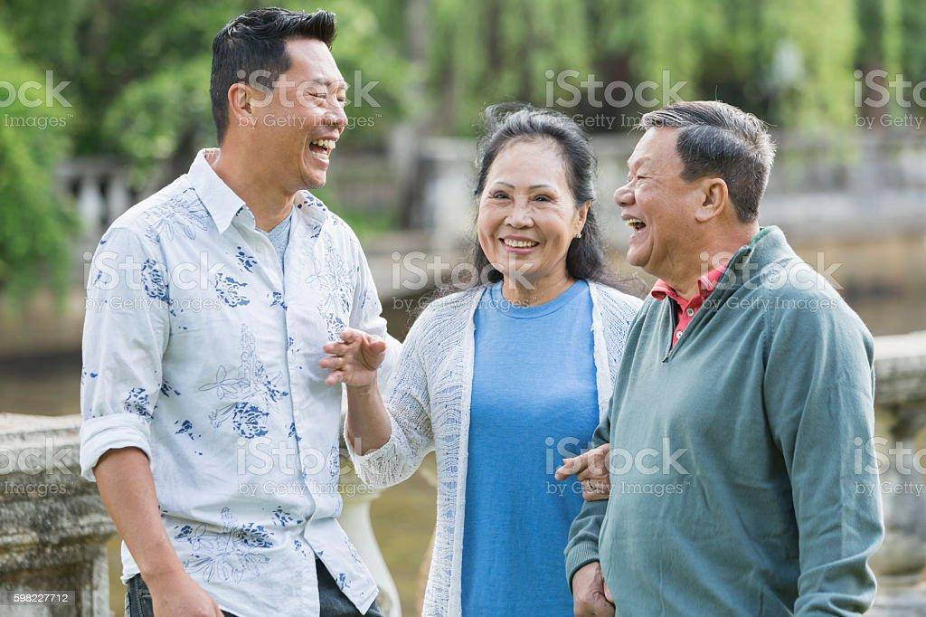 Homem asiático com pais sênior, caminhando no parque, sorrindo foto royalty-free