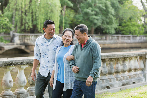 Asian man with senior parents in park walking An Asian man walking in the park with his parents. The mother is in the middle between her son and husband. They are talking and smiling. old mother son asian stock pictures, royalty-free photos & images