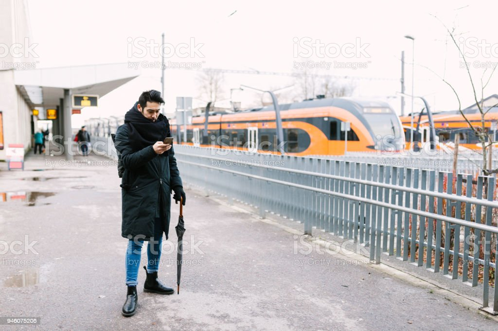 Asian man with umbrella on the railroad platform looking at phone stock photo