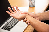 istock Asian man work so hard and long time that he has office syndrome. He has wrist pain, from working with laptop. 1263328880