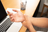 istock Asian man work so hard and long time that he has office syndrome. He has wrist pain, from working with laptop. 1263329143