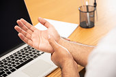 istock Asian man work so hard and long time that he has office syndrome. He has wrist pain, from working with laptop. 1263329312