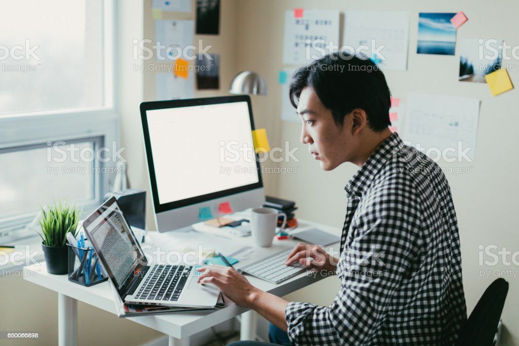 Asian man working at a comptuer stock photo