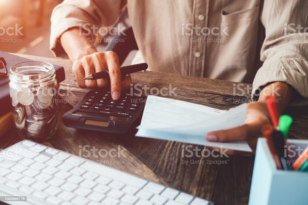 asian man working with calculator to calculate numbers expenses