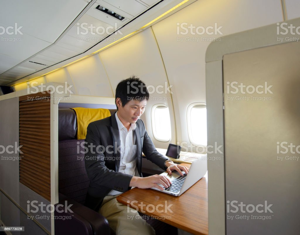Asian man working with laptop on first class airplane stock photo
