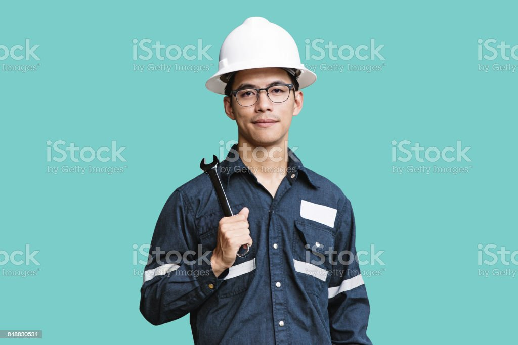 Asian man,Engineer or Technician in white helmet, glasses and blue working shirt suit holding wrench, isolated on green, mechanic and Oil and Gas industrial concept with clipping path. stock photo