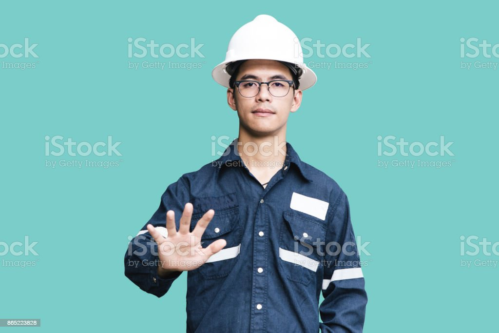 Asian man,Engineer or Technician in white helmet, glasses and blue working shirt suit pointing finger, isolated on white, mechanic and Oil and Gas industrial concept with clipping path. stock photo