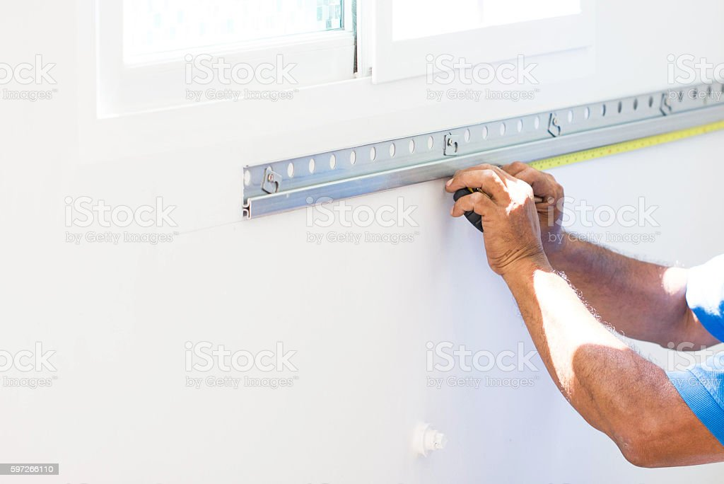 Asian Mans Hand Measuring A Wall With Measure Tape Lizenzfreies stock-foto