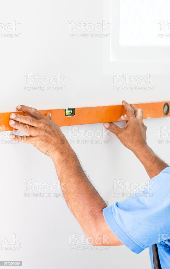 Asian Mans Hand Measuring A Wall With Spirit Level Lizenzfreies stock-foto