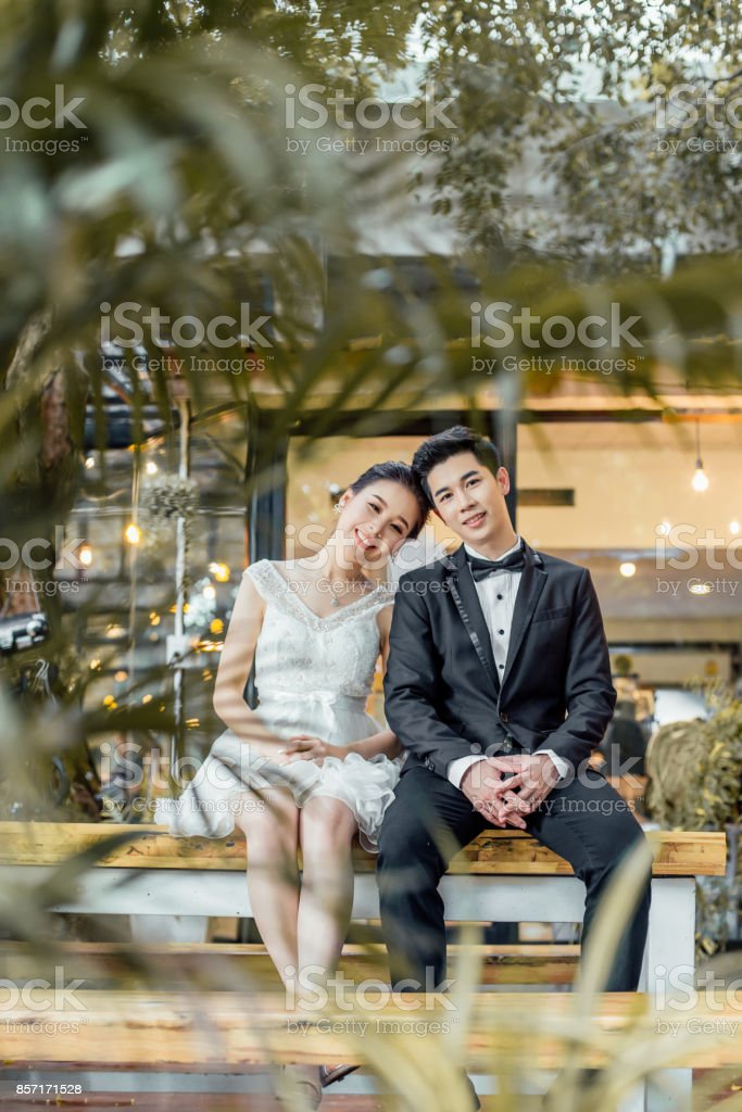 Asian married couple sit together at a restaurant. stock photo