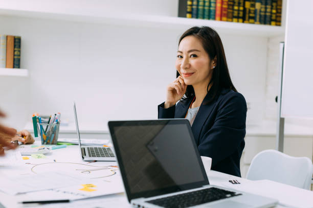 Asian mature business woman smiling and looking at camera while sitting in meeting stock photo