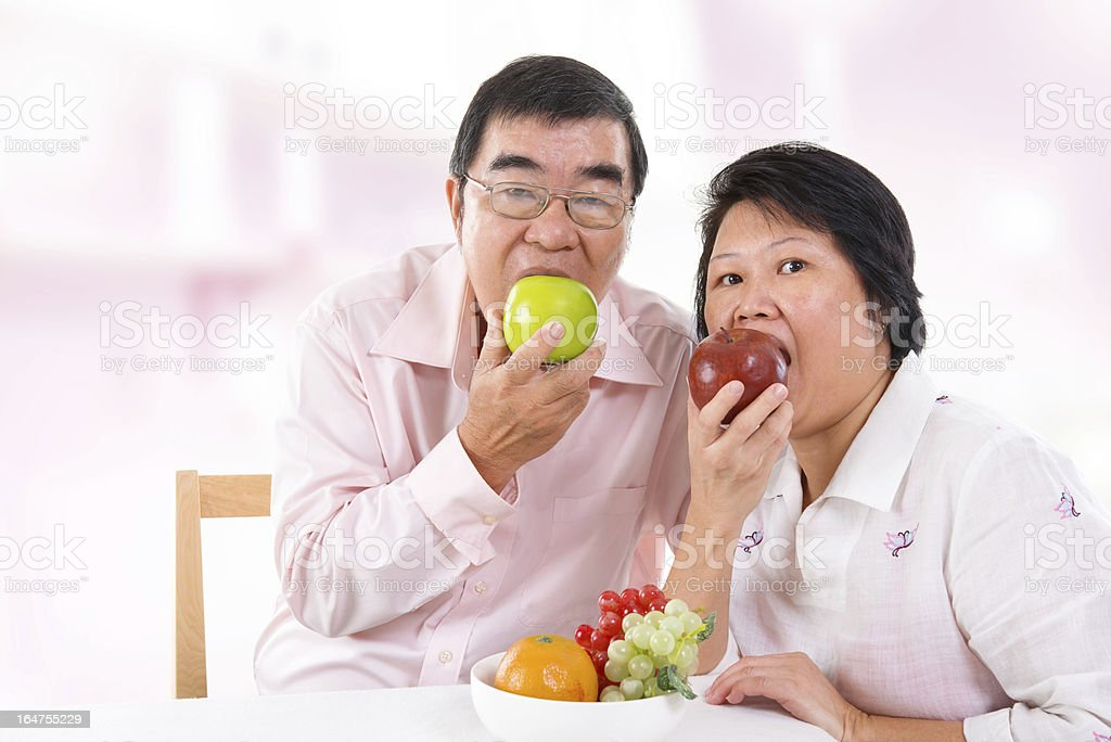 Asian mature couple eating apple royalty-free stock photo