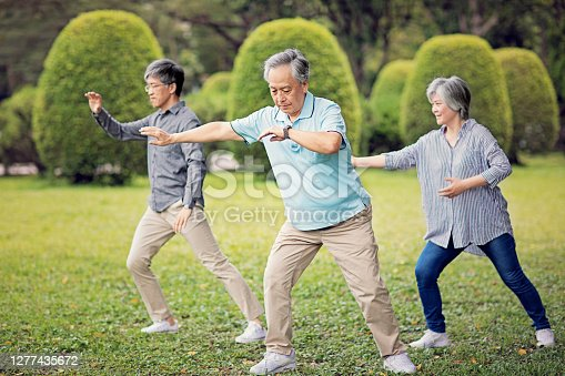 Asian mature friends are practicing Tai Chi in the park