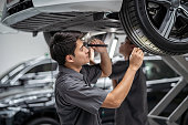 istock Asian mechanic Checking and torch tire in maintainance service center which is a part of showroom, technician or engineer professional work for customer, car repair concept 1179996623
