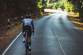 Asian men are cycling road bike in the morning.He is on a forest road.