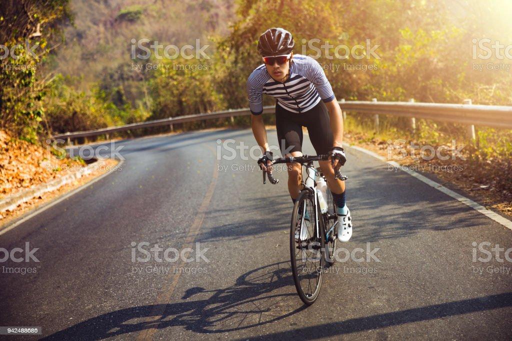 Aziatische mannen zijn racefiets fietsen in de ochtend. Hij is op de weg van een bos. foto